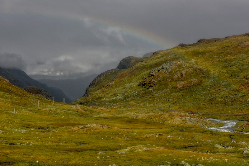 De regenboog tussen de bergen.
