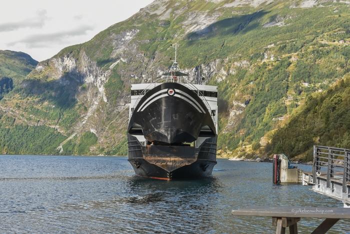 Als een wild dier met opengaande bek nadert de veerboot om aan te meren.