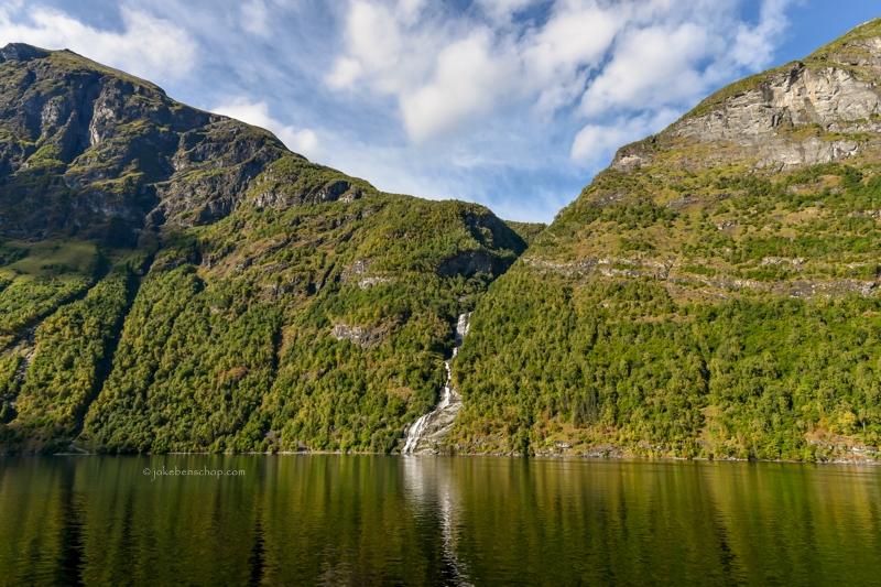 Hoge bergwanden met watervallen.