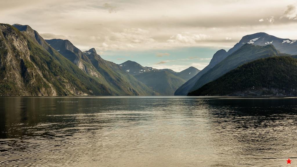 Het avondzonnetje speelt tussen de wolken door over het fjord.