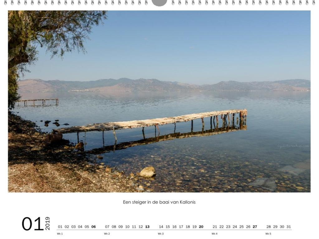 Uitzicht over de baai van Kallonis, een blauwe zee met oude houten steiger en in de wazige achtergrond de bergen.